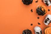 felülnézet az ízletes Halloween cupcakes a pókok és koponyák narancssárga háttérrel a másolási tér