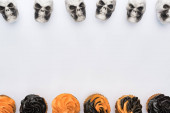 Photo top view of delicious Halloween cupcakes and skulls on white background with copy space