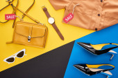 Photo top view of clothes, shoes and accessories with sale labels on blue, yellow and black background