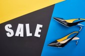 Photo top view of sale lettering near shoes on blue, yellow and black background