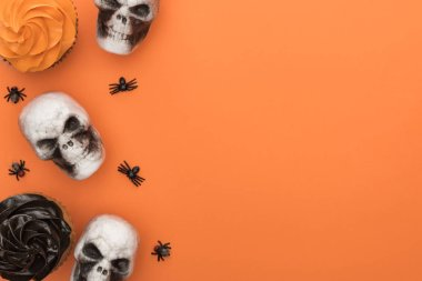 Top view of cupcakes, decorative skulls and spiders on orange background with copy space stock vector