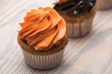 Selective focus of delicious Halloween orange cupcake on wooden table stock vector