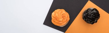 Top view of delicious Halloween cupcakes on black, orange and white background with copy space, panoramic shot stock vector