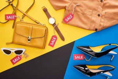 Elbise, ayakkabı ve aksesuarların mavi, sarı ve siyah arkaplan etiketli üst görünümü
