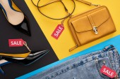 Photo top view of jeans, shoes and bag with sale labels on blue, yellow and black background