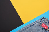 top view of jeans with sale label on blue, yellow and black background