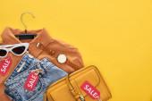 pohled na sáček, košili, brýle a džíny izolované na žluté
