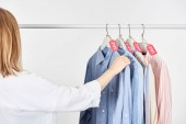 kivágott kilátás szőke nő közelében elegáns ingek lógott eladó címkék elszigetelt fehér