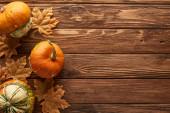 Draufsicht auf kleine Kürbisse auf brauner Holzoberfläche mit getrockneten Herbstblättern
