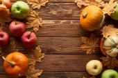 pohled na dýně a jablka na hnědém dřevěném povrchu se sušenými podzimním listím