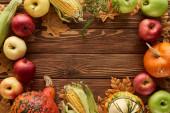 pohled na rám dýně, kukuřice cukrová a jablka na dřevěné ploše se sušenými podzimními listy