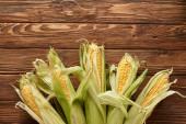 pohled na nevařenou sladkou kukuřici na dřevěném povrchu s prostorem pro kopírování