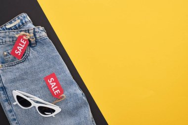 top view of jeans and glasses with sale labels on yellow and black background