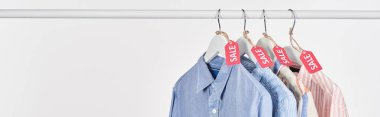 Elegant shirts hanging with sale labels isolated on white, panoramic shot stock vector