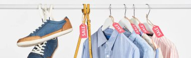 sneakers, bag and elegant shirts hanging with sale labels isolated on white, panoramic shot