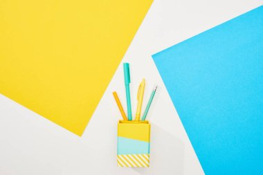Top view of colorful office supplies on yellow, blue and white background stock vector