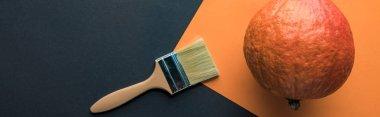 Panoramic shot of pumpkin near paintbrush on black and orange background stock vector