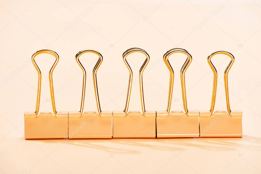 Row of paper clips on beige background stock vector