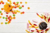 Photo top view of colorful gummy sweets, cupcakes and bonbons on white wooden table, Halloween treat