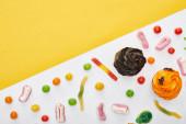felülnézet színes nyúm férgek közelében Cupcakes fehér és sárga háttér, Halloween kezelésére
