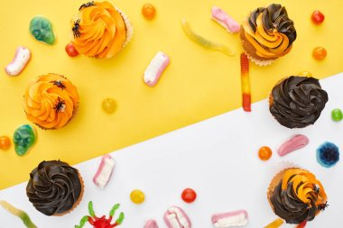 top view of colorful gummy sweets and cupcakes on yellow and white background with copy space, Halloween treat