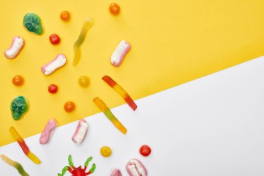 top view of colorful gummy sweets and bonbons on yellow and white background, Halloween treat