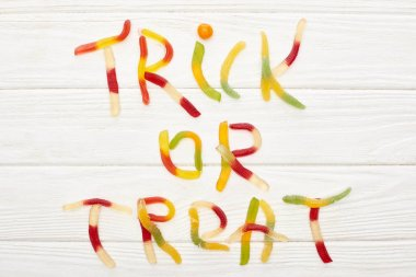 top view of trick or treat lettering made of colorful gummy sweets on white wooden table with spiders, Halloween treat