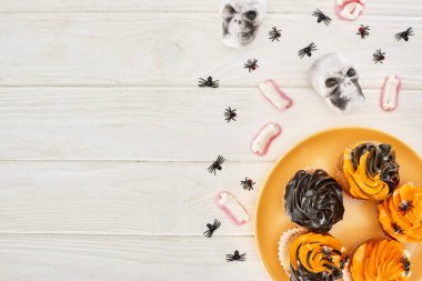 top view of cupcakes on orange plate, gummy teeth, skulls and spiders on white wooden table, Halloween treat