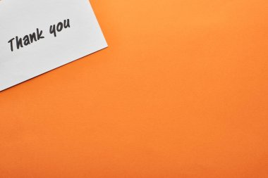 top view of thank you card on orange background