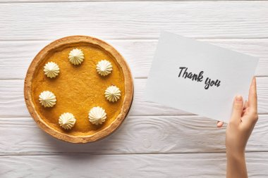 Cropped view of woman holding thank you card near pumpkin pie on wooden white table stock vector