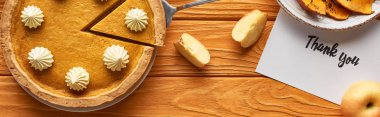top view of pumpkin pie with thank you card on wooden table with apples, panoramic shot