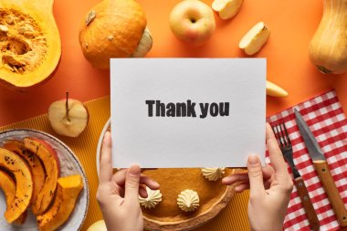 cropped view of woman holding thank you card near pumpkin pie on orange background