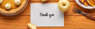 top view of delicious pumpkin pie, apples and thank you card on wooden orange table, panoramic shot