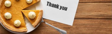 top view of delicious pumpkin pie and thank you card on wooden table, panoramic shot