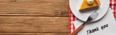 top view of tasty pumpkin pie and thank you card on plaid napkin on wooden rustic table, panoramic shot