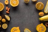 frame of yellow fruits and vegetables on grey textured background with copy space