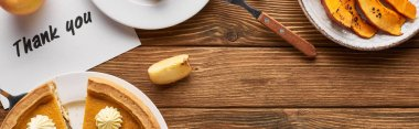 top view of tasty pumpkin pie, apples and thank you card on wooden rustic table, panoramic shot