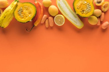 Top view of yellow fruits and vegetables on orange background with copy space stock vector