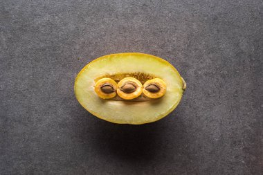 top view of melon and apricots on grey background with copy space
