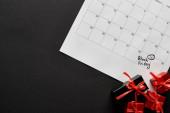 horní pohled na dárkové krabice a kalendář s černým pátečním datem na černém pozadí