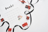 Fotografia top view of calendar with November 29 marked date on white background with black ribbon and presents