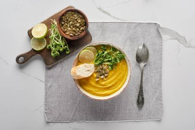 top view of autumnal mashed pumpkin soup ion napkin with spoon near ingredients on marble surface