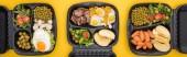 panoramatický záběr eko balíčků se zeleninou, jablky, masem, smaženými vejci a saláty izolovanými na žluté