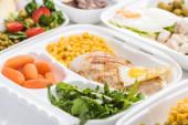 selektivní zaměření eko balení se zeleninou, masem, smaženým vejcem a rukolou na bílém pozadí