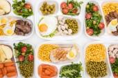 Fotografie shora pohled na eko balíčky s jablky, zeleninou, masem, smaženými vejci a saláty na bílém pozadí