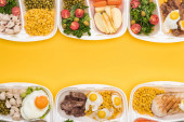 az almával, zöldségekkel, hússal, tükörtojással és sárgán izolált salátákkal ellátott ökocsomagok felülnézete