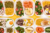 shora pohled na eko balení s jablky, zeleninou, masem, smaženými vejci a saláty izolované na žluté