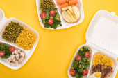 top view of eco packages with apples, vegetables, meat, fried egg and salads isolated on yellow