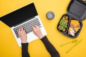 ořezaný pohled na ženu pomocí notebooku a eko balení s kukuřicí, masem, smaženými vejci a salátem, papírový kelímek izolovaný na žluté