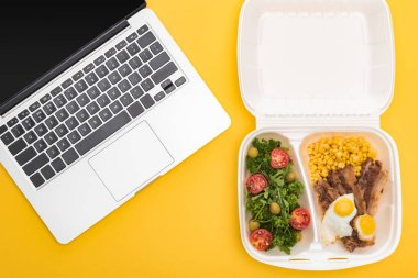 Top view of laptop and eco package with corn, meat, fried eggs and salad isolated on yellow stock vector